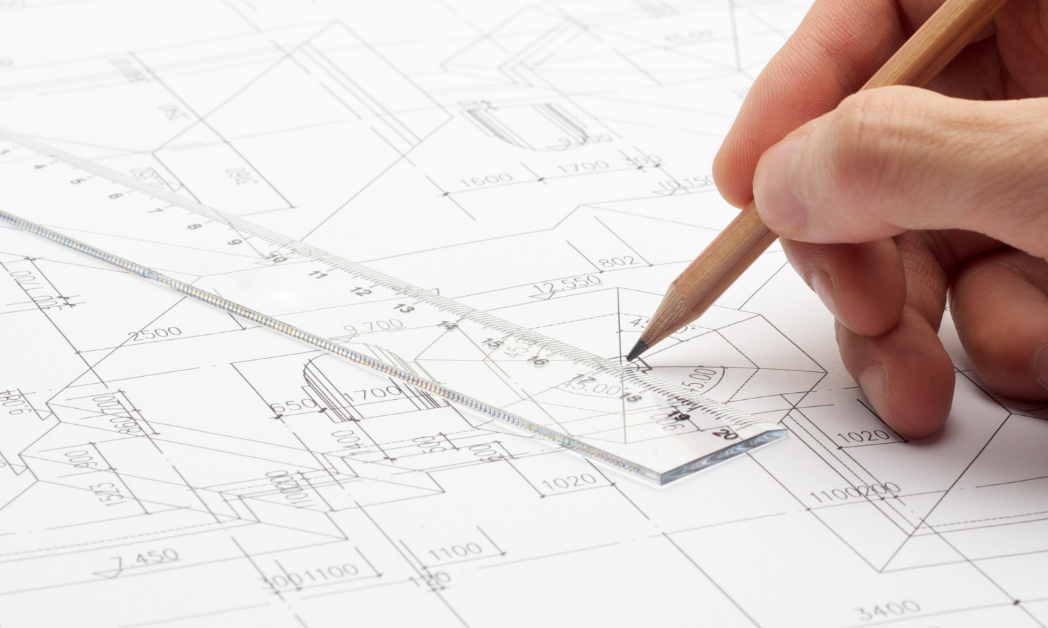 engineering sketch with clear 12 inch plastic ruler, hand holding a pencil, and a blueprint type part drawing on the table
