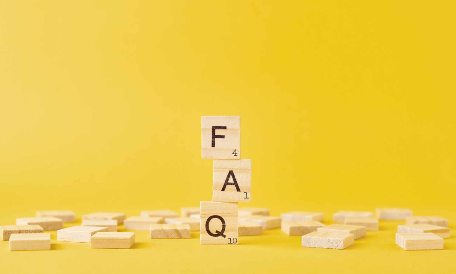image with gold background and wooden scrabble tiles spelling out FAQ