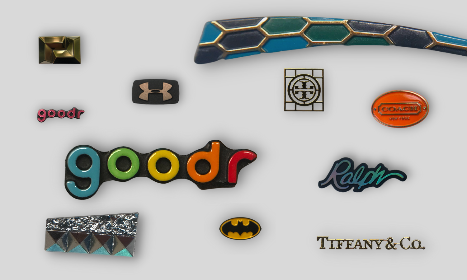 collage of small badges for eyewear: rainbow colored goodr; trans pink goodr; batman symbol, crushed glass/pyramid chrome, tiffany gold letters; tory burch gold letters, coach oval badge with orange background and gold copy, ralph script logo with black background and raised hologram copy, under armour square with black background and raw steel copy, mosaic trim piece with gold bridging and blue and green pieces