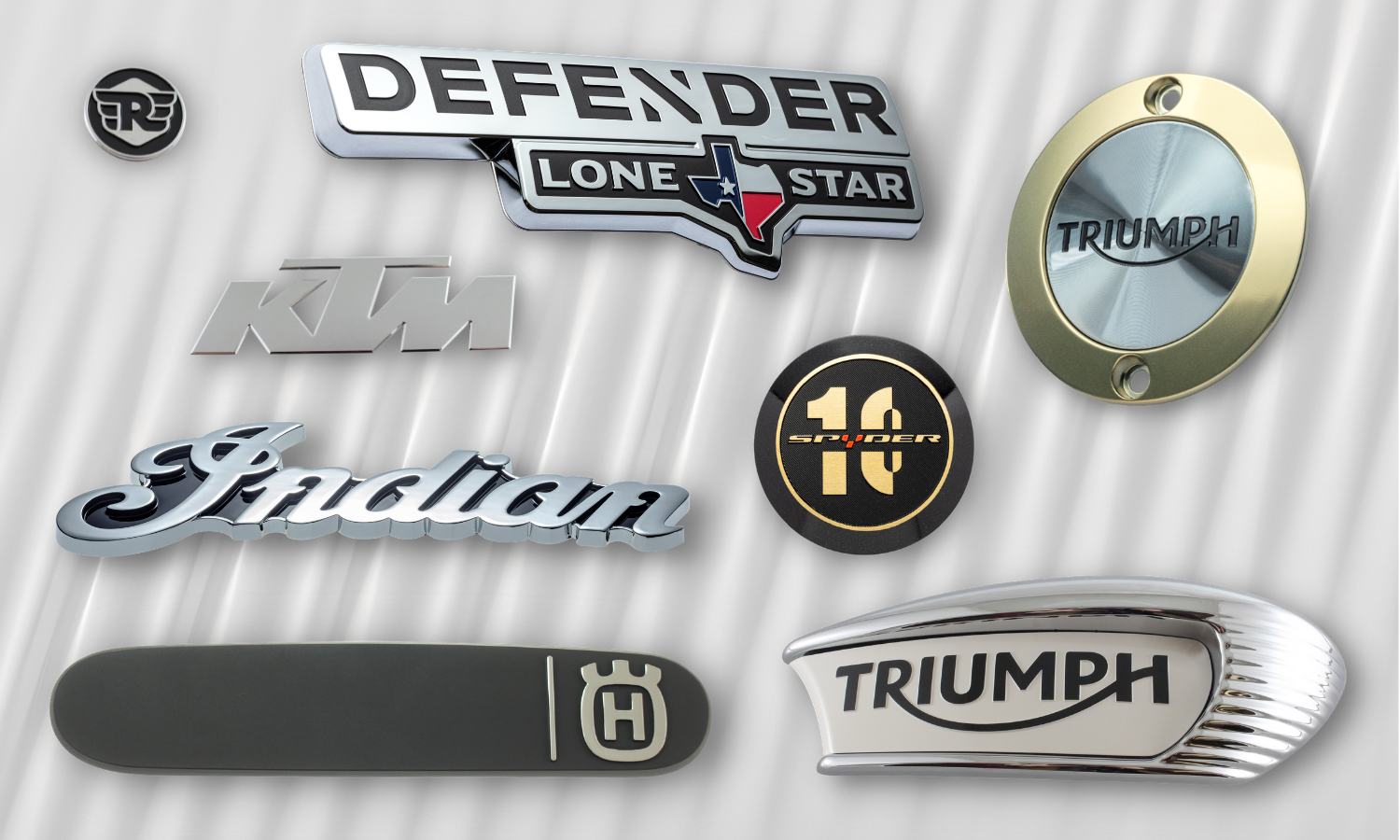 collage of parts that go on motorcycles; circle and oblong triumph motorcycle badges, chrome and black indian script badge, circle 10th anniversary black and gold spyder badge, chrome KTM badge, brushed black and chrome husqvarna trim badge, chrome and black defender lone star badge