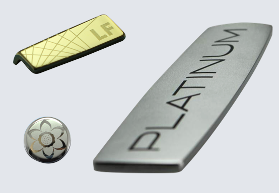 3 zinc name plates shown with alternating polished and matte sections. Gold plated small rectangle. Tiny circular part with flower pattern. Larger rounded rectangle with platinum text.