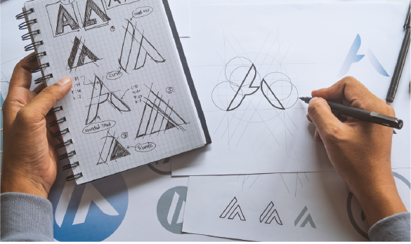 A hand sketching a logo shaped like an A using drafting paper and a pencil